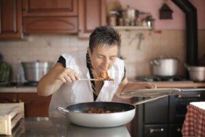 Vrouw in de keuken ruikt aan een pan met eten.