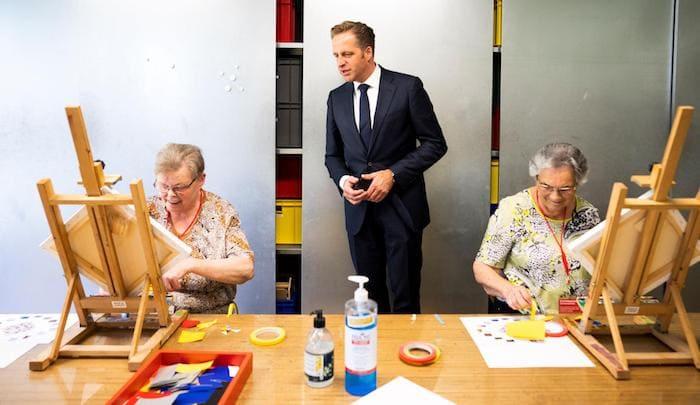 Minster Hugo de Jonge op bezoek bij twee oudere dames die zitten te schilderen.