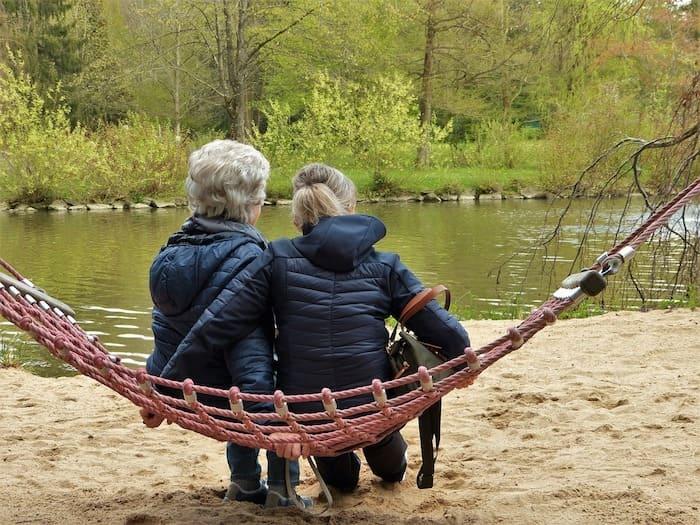 Moeder en dochter zitten samen aan het water.