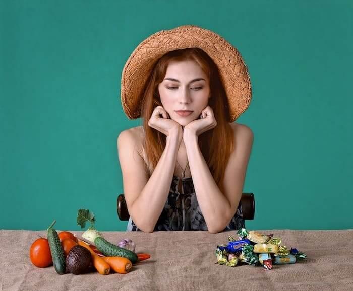 Vrouw zit aan tafel en kiest tussen snoep en groente